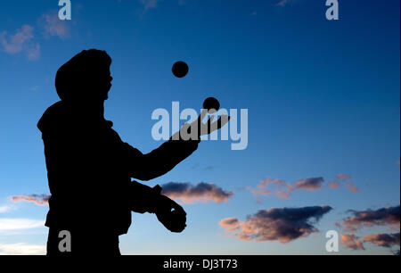 Dresden, Germany. 9th Nov, 2013. A man juggles with three balls in front of the backdrop of an Autumn evening sky - Stock Photo