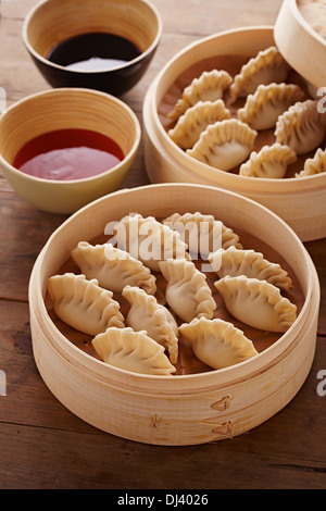 Homemade dim-sum asian dumplings on a traditional bamboo steamer - Stock Photo