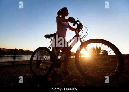 silhouette of young woman with bicycle outdoor - Stock Photo