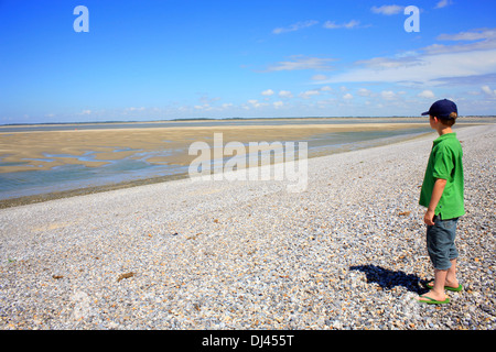 Boy looking out over Baie de la somme and Chenal de la Somme at Le Hourdel, somme, picardy, France - Stock Photo