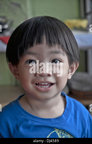 Beaming happy smiling Thai child with unusual large wide eyes. Thailand S.E. Asia - Stock Photo