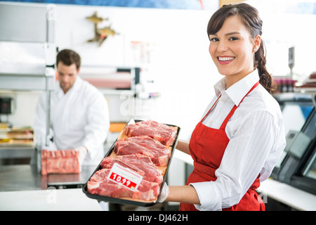 Happy Butcher Holding Meat Tray In Store - Stock Photo