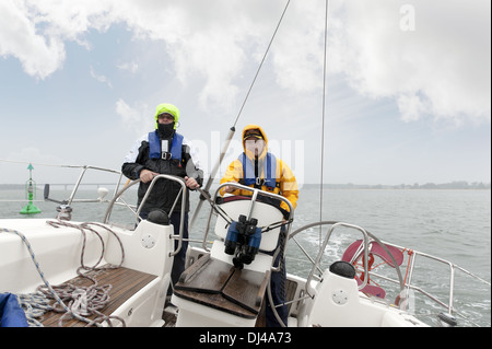 2 men standing at the stern of a yacht - Stock Photo