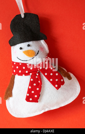 Snowman wearing red polka dot scarf and black top hat decoration ready for Christmas set on red background - Stock Photo