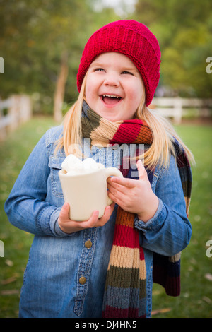 Cute Smiling Young Girl Wearing Hat and Scarf Holding Cocoa Mug with Marsh Mallows Outside. - Stock Photo