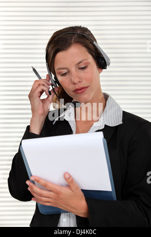 Woman adjusting her headset and holding a clipboard - Stock Photo