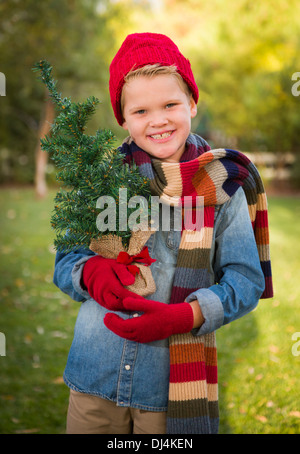Handsome Young Boy Wearing Holiday Clothing Holding Small Christmas Tree Outside. - Stock Photo
