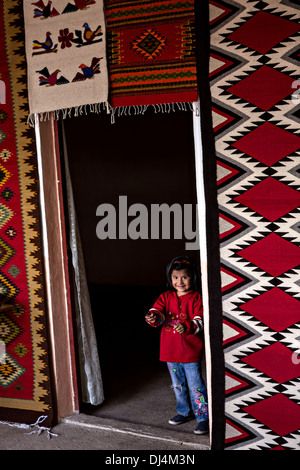 A young Zapotec indigenous girl smiles as she peaks out of a doorway at her families carpet weaving workshop October - Stock Photo