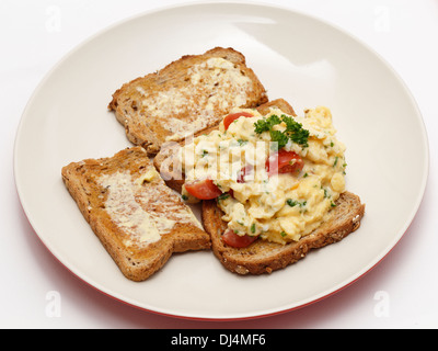 Scrambled egg on whole-grain toast with parsley and cherry tomatoes, - Stock Photo