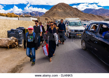 Buddhists walking to attend a teaching by His Holiness the 14th Dalai Lama at Choglamsar, Ladakh, Jammu and Kashmir - Stock Photo