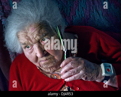 Worried elderly lady wearing an emergency call button alone at home talks anxiously on her telephone - Stock Photo