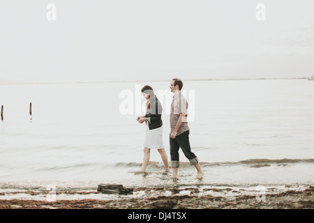 A Couple Walking Barefoot Along The Water's Edge; Crescent Beach, British Columbia, Canada - Stock Photo