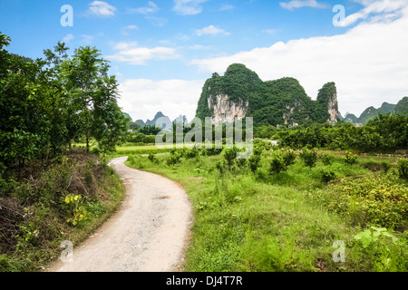 Road leading to limestone mountain in china - Stock Photo