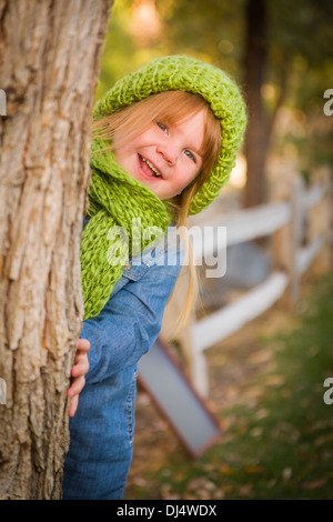 Cute Smiling Young Girl Wearing Green Scarf and Hat Posing for a Portrait Outside. - Stock Photo