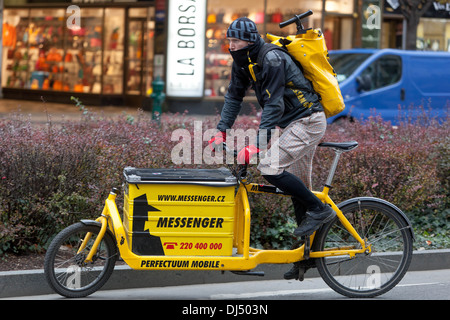 Male courier with bicycle delivering packages in city Prague, Czech Republic, Europe - Stock Photo