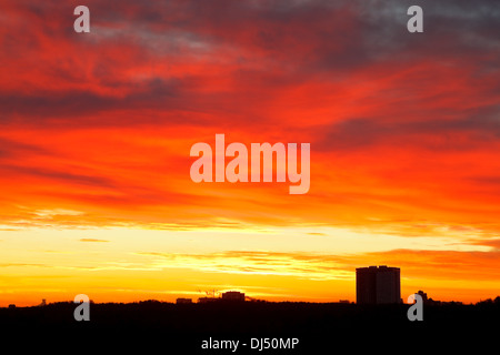 dramatic bright red, yellow, blue clouds in sunrise sky over urban houses - Stock Photo