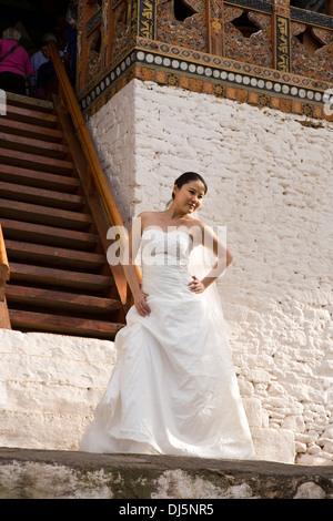 Bhutan, Punakha Dzong, Chinese woman in wedding dress posing for bridal portraits - Stock Photo