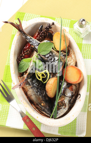 Oven baked mackerel and halved new potatoes in a casserole dish - Stock Photo