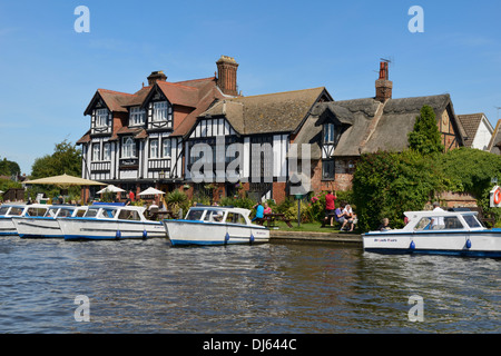 Boats moored on the river Bure, The Swan Inn Public House and restaurant, Horning, Norfolk, England, United Kingdom, - Stock Photo