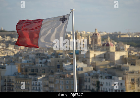 Flag of Malta with George Cross with the old city of Senglea in the background overlooking the Grand Harbour of - Stock Photo