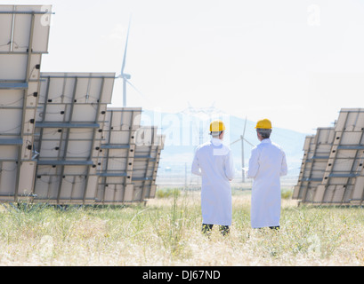 Scientists standing by solar panels in rural landscape - Stock Photo