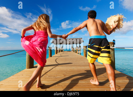 Young couple running on the wooden pier.  Nassau, Bahamas, Caribbean. - Stock Photo