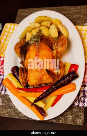 Stuffed Tasty Crispy Roast Chicken with carrots and potatoes - Stock Photo