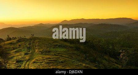 The sun sets over the Cardamom Hills near the small town on Kumily and overlooking the forests of Periyar near Kumily, - Stock Photo