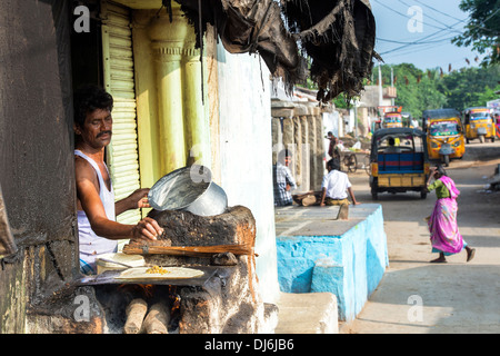 Indian man cooking masala dosa for people in a rural village. Andhra Pradesh, India - Stock Photo