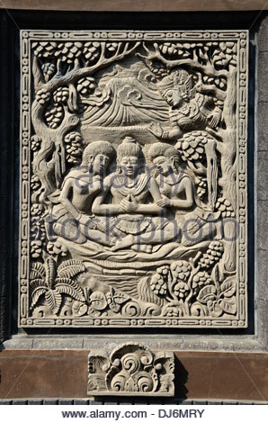 Relief carving panel on wall of Balinese Hindu temple depicting trinity of the three deities Brahma Shiva and Vishnui - Stock Photo