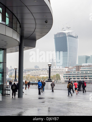 People near City Hall on the South Bank of the Thames and view of almost complete modern skyscraper (nicknamed the - Stock Photo