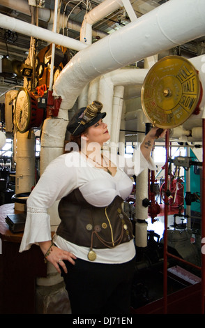 Young Woman Dressed in Steampunk Posing with Engine Room Controls on the Belle of Louisville - Stock Photo