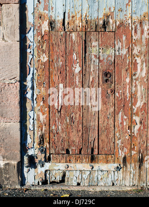 Old wooden door flaking paint Berwick upon Tweed, Northumberland, England, UK - Stock Photo