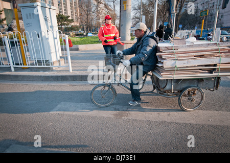 Man carrying planks on bicycle cart on street in Beijing, China - Stock Photo