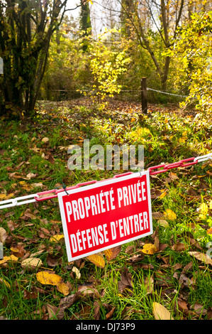 French Propriété Privée / Défence d'Entrer - Private Property / No Entry sign on plastic chain barrier in woodland. - Stock Photo