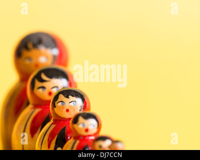 Group of russian matryoshka dolls in a row, with selective focus on one doll, set against a pale yellow background. - Stock Photo