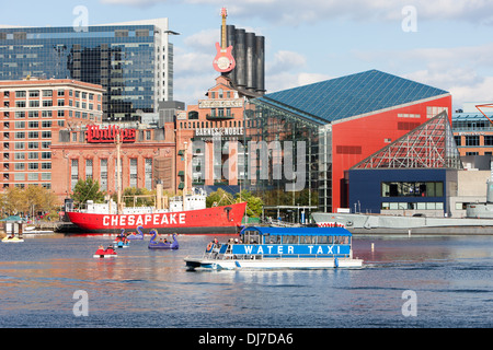 Tourists enjoy paddle boats as a Water Taxi approaches the Harborplace landing in the Inner Harbor of Baltimore, - Stock Photo