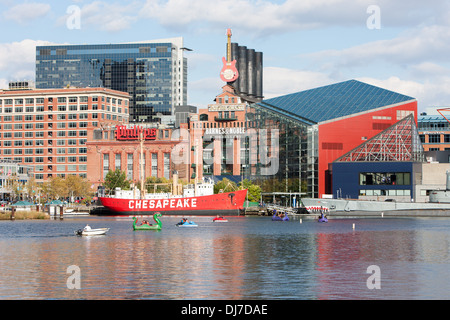 Tourists enjoy paddle boats near the National Aquarium and Lightship Chesapeake in the Inner Harbor in Baltimore, - Stock Photo