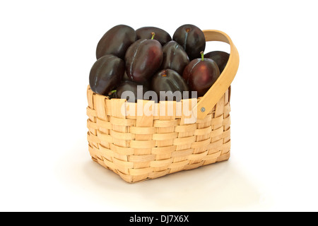 Plums in a wicker basket isolated on a white background - Stock Photo