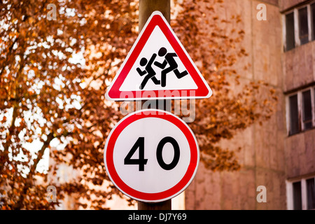 Road sign with running children and a 40 speed limit sign on an autumn street. - Stock Photo