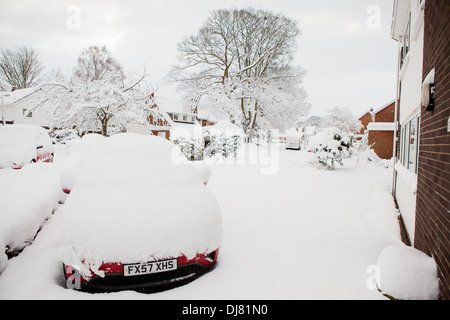 A car covered in deep snow, parked on the driveway of a house - Stock Photo