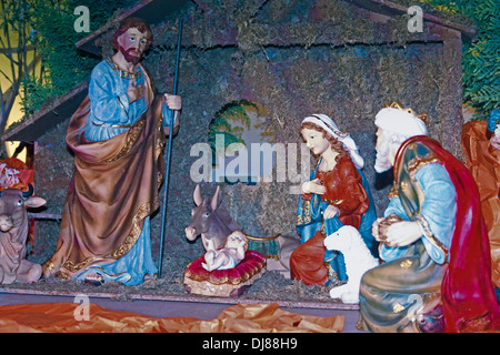 Christmas nativity scene of Jesus birth in an old cottage nearby Bethlehem with Joseph, mary and three shepherd - Stock Photo