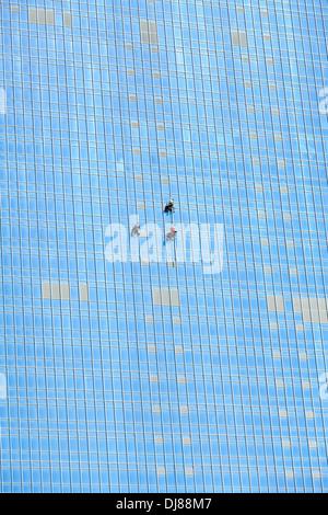 Industrial climbers working on mirror skyscraper facade - Stock Photo
