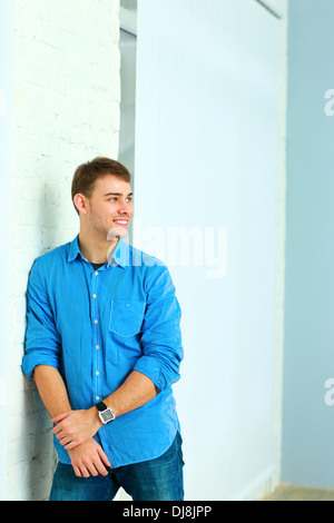 Portait of young happy businessman standing near the wall at office - Stock Photo