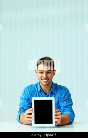 Young businessman showing display of tablet computer