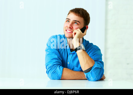 Young cheerful businessman talking on the phone and looking up at copyspace in office - Stock Photo