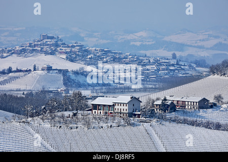 Small towns and vineyards on the hills covered with snow in Piedmont, Northern Italy. - Stock Photo
