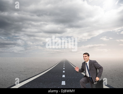 Happy businessman holding a briefcase and running - Stock Photo