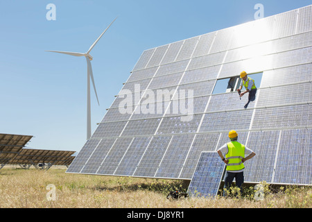 Workers examining solar panel in rural landscape - Stock Photo