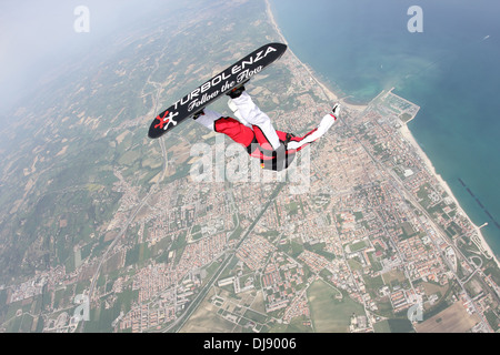 Skydiver is surfing the blue sky over the deep blue sea. Skysurfer is spinning in a helicopter move along the shore - Stock Photo
